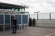 As a Virgin jet takes off overhead, airline employees stop for a cigarette break near the smoking shelter at Heathrow's T5.