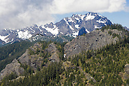 Mount Constance in the Olympic Mountains from about five miles distance looking west with a long lens in mid June in a heavy snow year