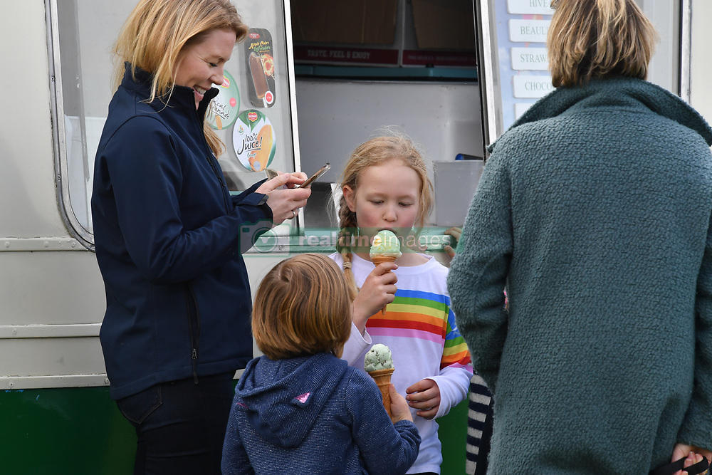 Autumn Phillips watches Savannah Phillips and Mia Tindall enjoying ice creams during the Land Rover Novice & Intermediate Horse Trials at Gatcombe Park on March 23, 2019.