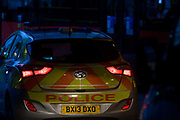 The rear of a Metropolitan Police car is lit by headlights from another vehicle, in the London borough of Southwark. The car is a Hyundai i30 that forms part of the Met's car fleet for 2013. Alongside flashing blue and red lights, the vehicle's reflective stripes are designed especially to enhance the car's visibility in moments of emergency. The car here has stopped in heavy traffic on the southern side of London Bridge