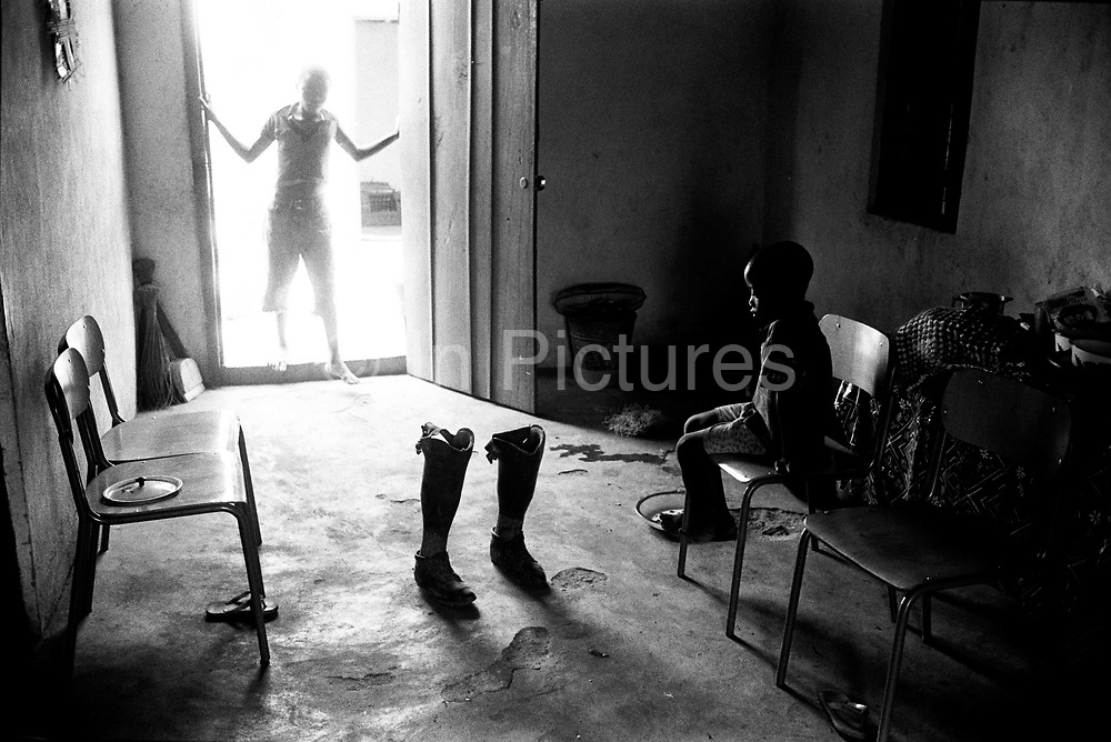 A boy ponders his father's articicial legs, Makeni, Sierra Leone 2004<br /> Rebel forces, the Revolutionary United Front in Sierra Leone, systematically murdered, mutilated, and raped civilians during the country's civil war as a policy of terror
