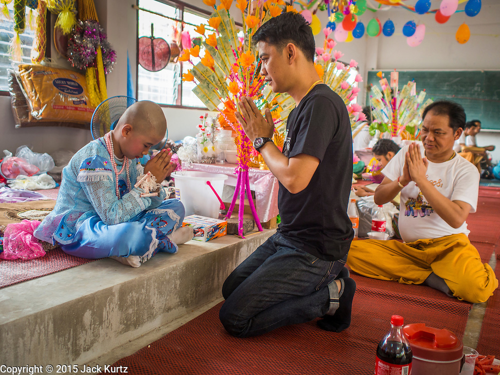 """05 APRIL 2015 - CHIANG MAI, CHIANG MAI, THAILAND:  A Tai Yai boy being ordained as a Buddhist novice prays with members of his family during the second day of the three day long Poi Song Long Festival in Chiang Mai. The Poi Sang Long Festival (also called Poy Sang Long) is an ordination ceremony for Tai (also and commonly called Shan, though they prefer Tai) boys in the Shan State of Myanmar (Burma) and in Shan communities in western Thailand. Most Tai boys go into the monastery as novice monks at some point between the ages of seven and fourteen. This year seven boys were ordained at the Poi Sang Long ceremony at Wat Pa Pao in Chiang Mai. Poy Song Long is Tai (Shan) for """"Festival of the Jewel (or Crystal) Sons.   PHOTO BY JACK KURTZ"""