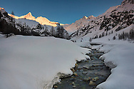 A wintry view of the top of the Valsaverenche, one of the many valleys within the Gran Paradiso national Park in Valle d'Aosta, italy. The beautiful peak known as Becca di Monciair, part of the Gran Paradiso range, shines in the warm sunset light in the background.