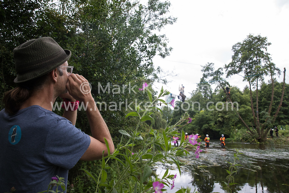 Denham, UK. 24 July, 2020. A videographer shouts detailed safety instructions to a tree surgeon working with the National Eviction Team felling an ancient alder tree for the HS2 high-speed rail link to which activists were attached on a line above the shallow river Colne. An operation involving officers from the Metropolitan Police, Thames Valley Police, City of London Police and Hampshire Police ensured the removal of the tree.