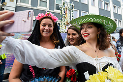 © Licensed to London News Pictures. 21/07/2019. LONDON, UK.  Participants take a selfie ahead of the Procession of Our Lady of Mount Carmel, starting at St Peter's Italian Church and then around the streets of Clerkenwell.  Floats carry life size depictions of Biblical scenes in a Catholic festival which has taken place annually for 100 years in the area which was once the capital's Little Italy.  Photo credit: Stephen Chung/LNP