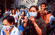 "NEW YORK, NY: Tourists with dust masks look at the wreckage of the World Trade Center from a vantage point on Liberty Street in lower Manhattan near ""Ground Zero"" of the World Trade Center complex after the WTC terrorist attack, Sept. 22, 2001. More than 2,900 people were killed when terrorists crashed two airliners into the towers on Sept. 11, 2001. Everything for miles around the WTC was covered in dust and ash when the 110 story tall towers collapsed. PHOTO BY JACK KURTZ"