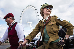 © Licensed to London News Pictures. 04/05/2019. London, UK. A woman passes the London Eye as she cycles across Westminster Bridge on the Tweed Run bike ride in Central London. The annual event sees hundreds of people cycle around the capital past various landmarks wearing vintage tweed outfits. Photo credit: Rob Pinney/LNP