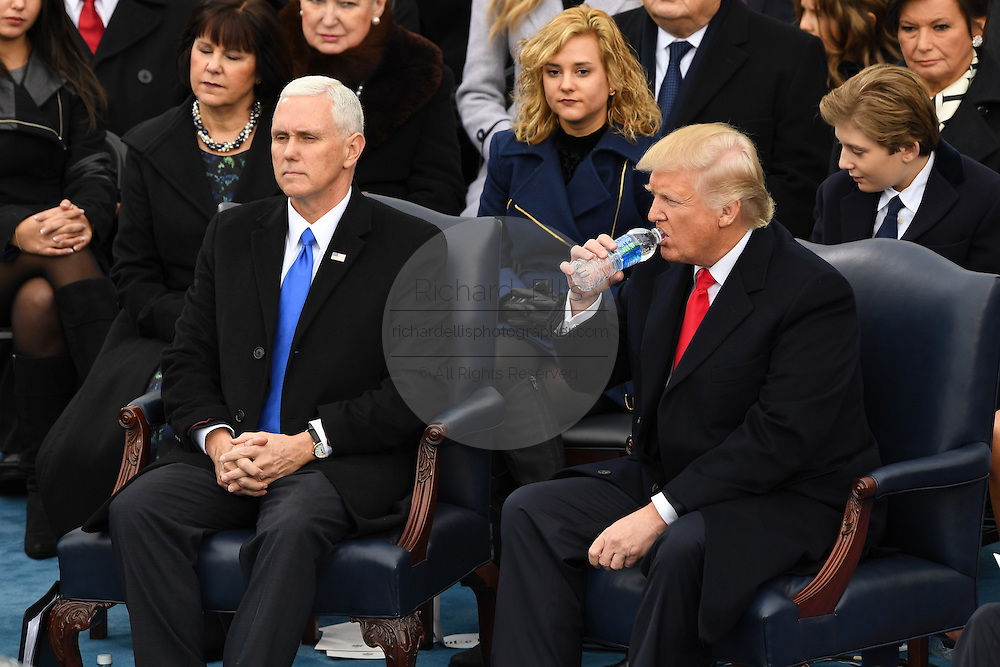 President Donald Trump sitting with Vice President Mike Pence takes a drink of water during the Inaugural ceremony to become the 45th President of the United States January 20, 2017 in Washington, DC.