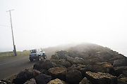 A jeep drives up Ediz Hook towards thick marine fog in Port Angeles Harbor, Washington.