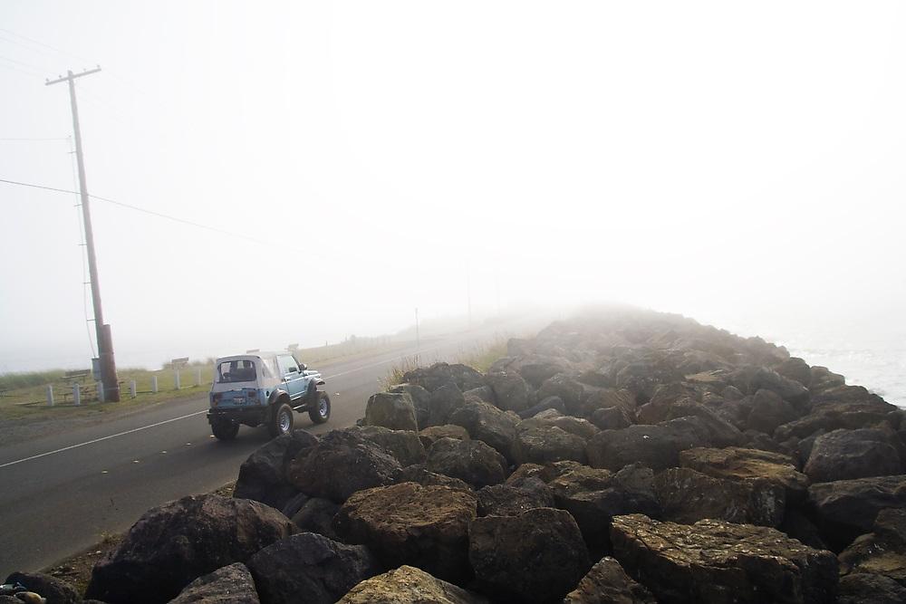 A jeep drives up Ediz Hook towards thick marine fog in Port Angeles Harbor, Washington.