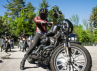 Lilly James from the Orlando Iron Lilies puts on her gloves as their group ride to the Kancamagus Highway leaves from Laconia Harley Davidson on Tuesday morning.  (Karen Bobotas/for the Laconia Daily Sun)