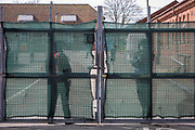 Security guards ready to open the gate to the first taxi arrives of the new intake of asylum seekers arrive at Napier barracks on the 9th of April 2021 in Folkestone, United Kingdom. Despite many criticisms of the site including a damning report from the HM Inspectorate of Prisons declaring the camp filthy and impoverished and Public Health England declaring the accommodation unsuitable durning a pandemic the Home Office continues to place vulnerable people in the former military barracks.