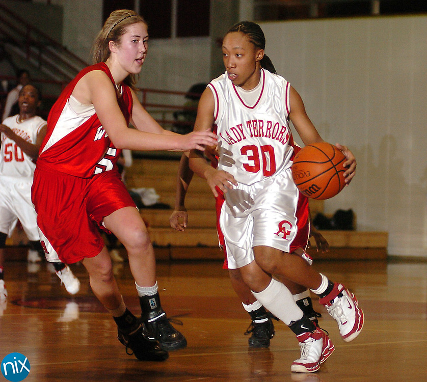 Glynn Academy's Valencia Kelly, 30, tries to drive on Woodward Academy's Bianca Whitten, 5, during Woodwards' 76-63 win over the Red Terrors in the first round of the state playoffs Friday night.