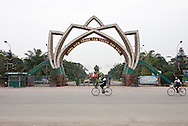 Concrete gate with a lotus shape in Vinh, Vietnam, Asia. Two teenagers come back from school riding their bicyle.