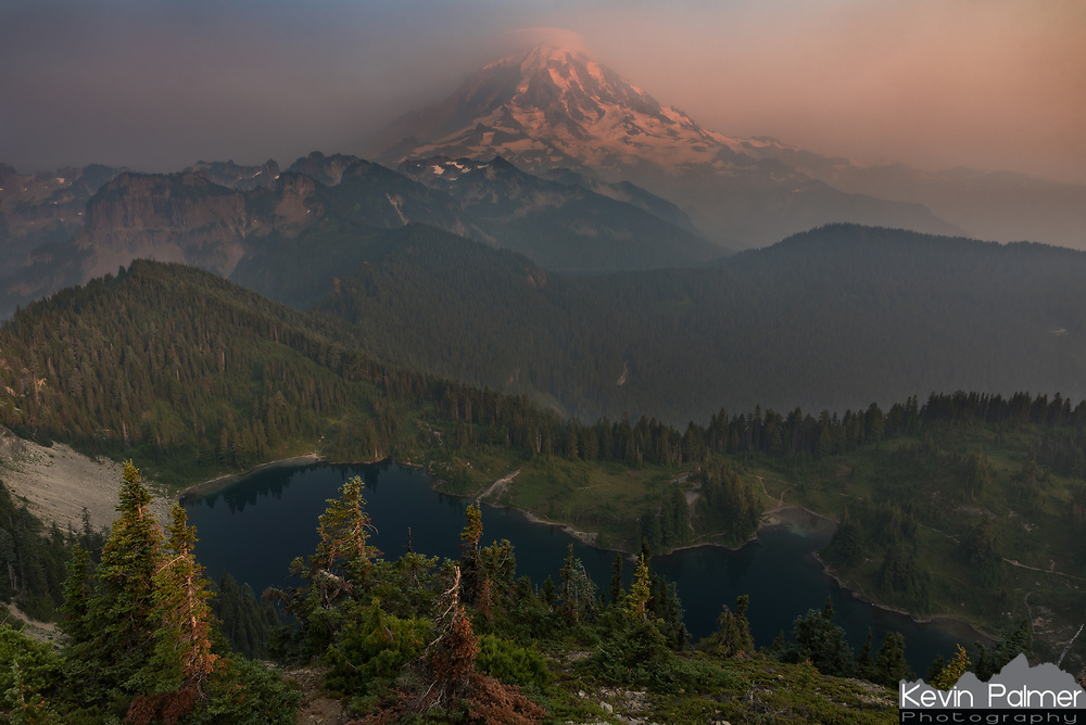 The view from Tolmie Peak is spectacular, or at least it would be without the smoke. Eunice Lake sits in a valley below, while Mount Rainier rises above the forested ridges.