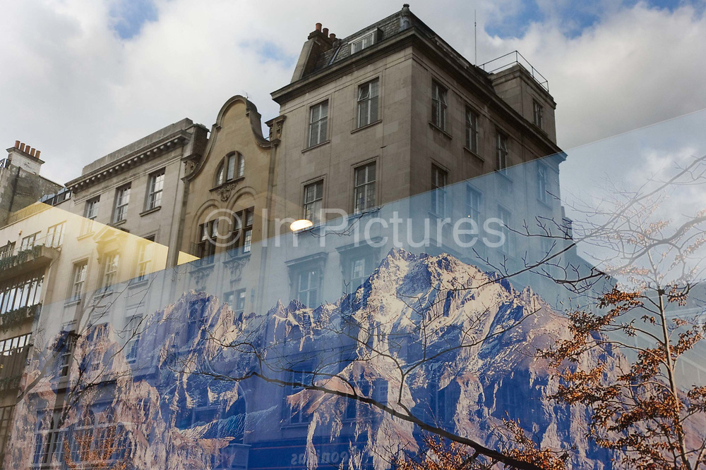 The imagery of the great outdoors against the urban environment seen through a shop window in central London. In the foreground is a large image of snow-covered mountain peaks in the Alps or another range of geological tops formed over millennia - bare branches below the tree line also making their presence. Above them in an incongruous landscape of nature versus nature are buildings along Bond Street, a fashionable fashion and art area. We see the edifices of a man-made society and architecture and the rawness and beauty of the natural world together in one framed window. Man's achievements within the urban city seen in context with the forces of a natural, uncontrollable environment that we as humans are powerless to harness.