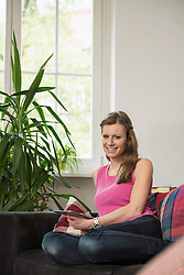 Portrait of a young woman using digital tablet in living room and smiling, Munich, Bavaria, Germany