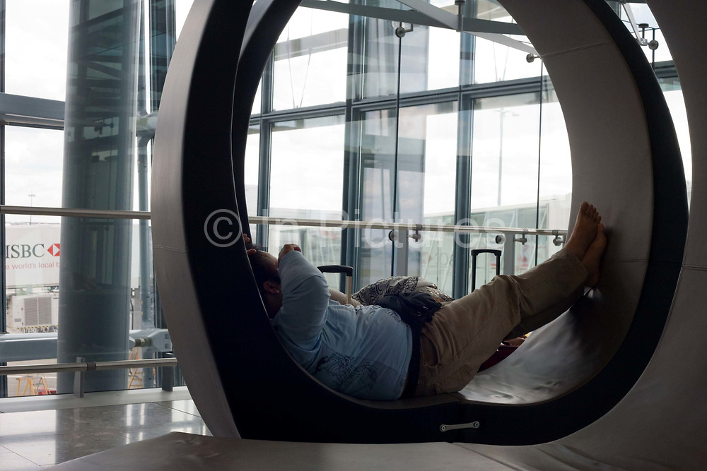"""A resting passenger sleeps on a specially-designed circular couch near airport gates during his layover transit period at Heathrow airport's Terminal 5. The man has jet lag after a long-haul flight across continents and now needs to re-adjust to British Summer time (BST). Vast sheets of window glass lets in natural daylight in this tranquil area where travellers can remain largely undisturbed from the otherwise hectic airport terminal created by the Richard Rogers Partnership (now Rogers Stirk Harbour and Partners). From writer Alain de Botton's book project """"A Week at the Airport: A Heathrow Diary"""" (2009)."""