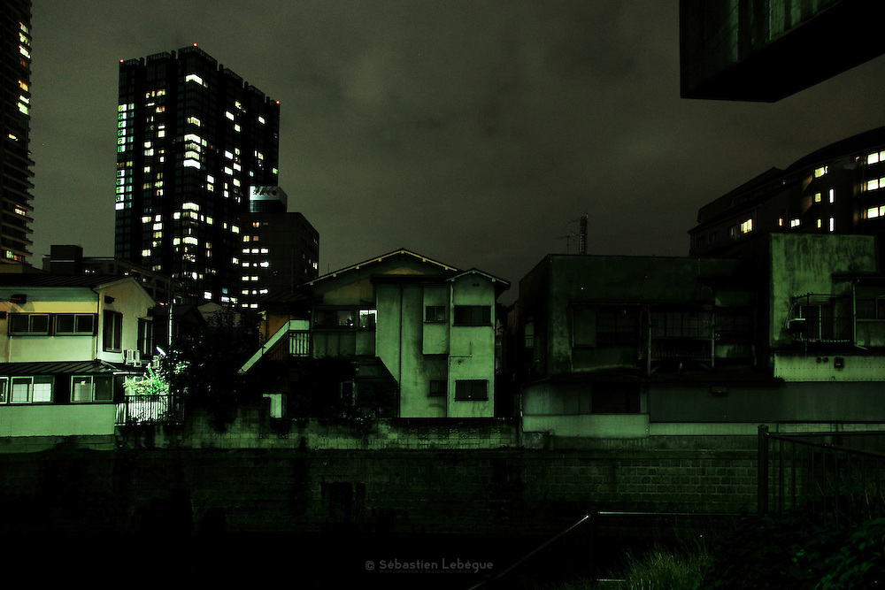 TOKYO, JAPAN, 1 NOVEMBER - Small houses in front of a river and under highway. The Shuto expressway loop line overhang habitation's area and follow the river's waterway. November 2010
