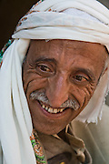 A close up of Ahmed Ahmed Swaid, a qat merchant in the old Yemeni city of Sanaa. (Ahmed Ahmed Swaid is featured in the book What I Eat: Around the World in 80 Diets.) The caloric value of his typical day's worth of food in the month of April was 3300 kcals. He is 50 years of age; 5 feet, 7 inches tall; and 148 pounds. Ahmed, who wears a jambiya dagger as many Yemeni men do, has been a qat dealer in the old city souk for eight years. Although qat chewing isn't as severe a health hazard as smoking tobacco, it has drastic social, economic, and environmental consequences. When chewed, the leaves release a mild stimulant related to amphetamines. Qat is chewed several times a week by a large percentage of the population: 90 percent of Yemen's men and 25 percent of its women. Because growing qat is 10 to 20 times more profitable than other crops, scarce groundwater is being depleted to irrigate it, to the detriment of food crops and agricultural exports. MODEL RELEASED.