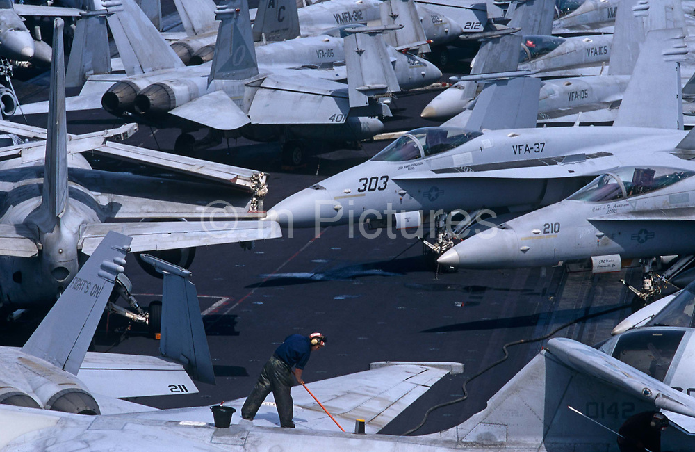 Up on the top deck, we see a lone sailor brushing off the grubby surfaces of parked F/A-18C Hornets and S-3 Vikings on the US Navy aircraft carrier USS Harry S Truman during its deployment patrol of the no-fly zone at an unknown location in the Persian Gulf. Stacked together in tight formation to fit them all together during a daytime break in operations, the man bends into his task during the hottest time of day. The Truman is the largest and newest of the US Navy's fleet of new generation carriers, a 97,000 ton floating city with a crew of 5,137, 650 are women. The Iraqi no-fly zones (NFZs) were proclaimed by the United States, United Kingdom and France after the Gulf War of 1991 to protect humanitarian operations in northern Iraq and Shiite Muslims in the