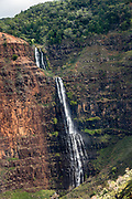 """Waipoo Falls plunges in a cascade for 800 feet in Waimea Canyon State Park (here seen via helicopter) on island of Kauai, Hawaii, USA. Waimea Canyon (""""the Grand Canyon of the Pacific"""") slices as much as 3000 feet deep across ten miles of western Kauai. About 4 million years ago, a catastrophic collapse of the volcano that created Kauai created a fault which was gradually cut deeper by the Waimea River, fed by extreme rainfall on the island's central peak, Mount Wai'ale'ale, among the wettest places on Earth. Waimea is Hawaiian for """"reddish water,"""" referring to the local orange clay."""