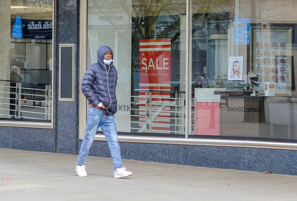 24th February, Cheltenham, England. A man smokes a cigarette with his mask pulled down in the Promenade area in Cheltenham during the third national lockdown.