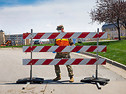 "26 APRIL 2020 - DES MOINES, IOWA: A soldier with the Iowa Army National Guard opens the gate of the COVID-19 drive through testing site in Des Moines. Iowa started mass testing Saturday, with a drive through testing site in a parking lot in downtown Des Moines. The testing this weekend is considered a ""soft opening"" for the program and tests were reserved for medical professionals and first responders. Despite numerous outbreaks in meat packing plants throughout Iowa, members of the public have not been able to get tested. On Saturday, 25 April, there were 5,092 confirmed cases of COVID-19 (Coronavirus / SARS-CoV-2) in Iowa (an increase of 647 since Friday, April 24) and 112 deaths in Iowa caused by COVID-19.                PHOTO BY JACK KURTZ"