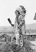 9305-B7326A.  Chief Tommy Thompson at end of long house in Celilo Village. April 16, 1939. Celilo Falls, Oregon