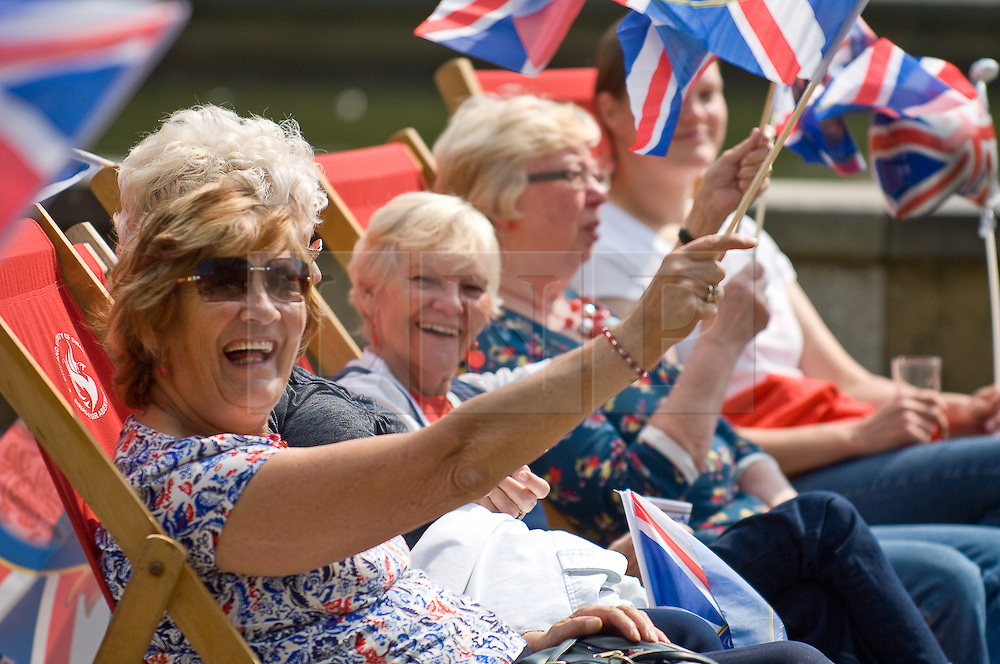 LOCATION, UK  29/04/2011. The Royal Wedding of HRH Prince William to Kate Middleton. A group of ladies wave a flags in the sunshine at  castle square in Swansea where crowds have gathered to watch the wedding on a giant screen. Photo credit should read Aled Llywelyn/LNP. Please see special instructions. © under license to London News to London News Pictures