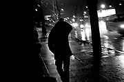 A man leaves City Team Ministries into a late-winter rain storm after the free community dinner. City Team serves food to more people than it can house and on any given night there are a dozen or more men turned away.