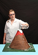 A young girl demonstrates her paper mache volcano reacting with vinegar and baking soda. This is an acid - base neutralization reaction which produces water and a salt as reactants.