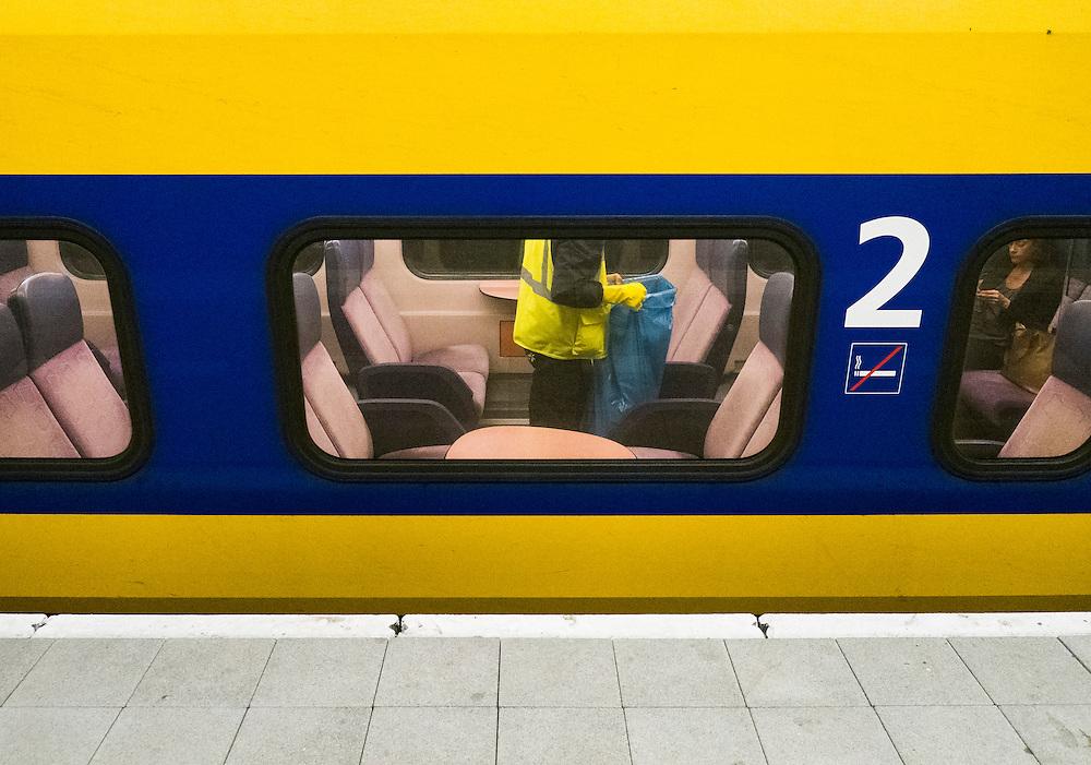Nederland, Den Haag, 25 sept 2013<br /> Schoonmaker in trein loopt met vuilniszak door de wagon om afval op te ruimen.<br /> Foto(c): Michiel Wijnbergh