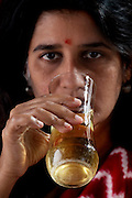 Millie Mitra, a vegan, who has a thirst for alternative medicine and homeopathic healing, drinks a glass of urine at her home in Benson Town, Bangalore, India. (Millie Mitra is featured in the book What I Eat: Around the World in 80 Diets.)  She has practiced Shivambu (sometimes spelled Sivambu), which is the drinking of one's own first morning urine (200 cc in her practice) as a curative and preventative measure, for over 15 years. Millie applies urine to her skin as well, for the same reasons. Her husband Abhik has tried Shivambu and she helped her children to practice it when they were young, but currently only Millie practices urine therapy. MODEL RELEASED. .