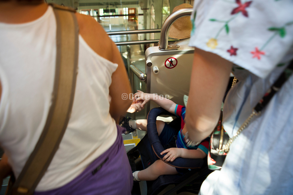 parents with toddler in a stroller on a crowded public train