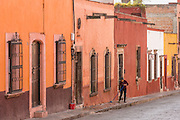 A woman washes the sidewalk along Zapateros Street in the historic center of San Miguel de Allende, Mexico.