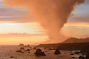 Smoke from the Meyers Fire rises above California's Sonoma Coast on Tuesday evening, August 18, 2020 after a lightning storm pummeled Northern California starting hundreds of wildfires across the region.
