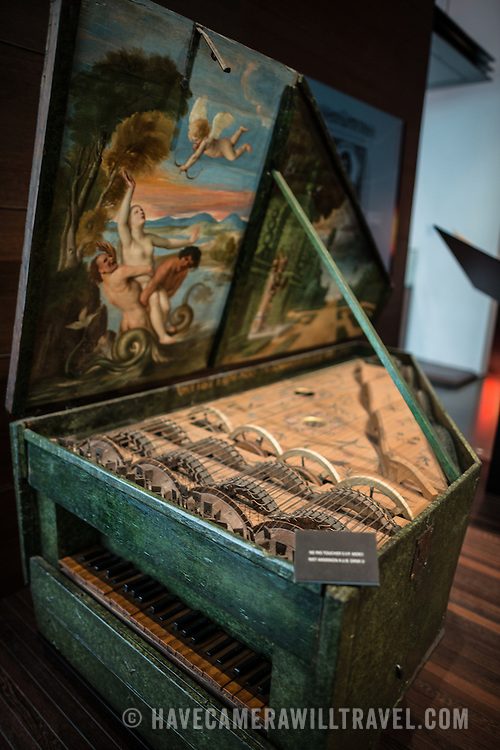 A keyboard instrument known as a Geigenwerk, dated to 1625, on display at the Musical Instrument Museum in Brussels. The Musee des Instruments de Musique (Musical Instrument Museum) in Brussels contains exhibits containing more than 2000 musical instruments. Displays include historical, exotic, and traditional cultural instruments from around the world. Visitors to the museum are given handheld audio guides that play musical demonstrations of many of the instruments. The museum is housed in the distinctive Old England Building.