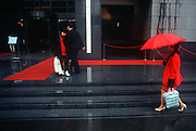 While still a British colony, a red 1990s theme of carpet, rope barrier, umbrella and clothing outside the Bank of China, on 21st April 1995, in Central, Hong Kong, China.