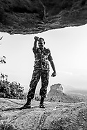 A member of the Sri Lankan air force stands on Pidurangala Rock, a mountain peak best known for its excellent view of the famous Sigiriya rock fortress, seen in the distance.<br />(April 5, 2017)