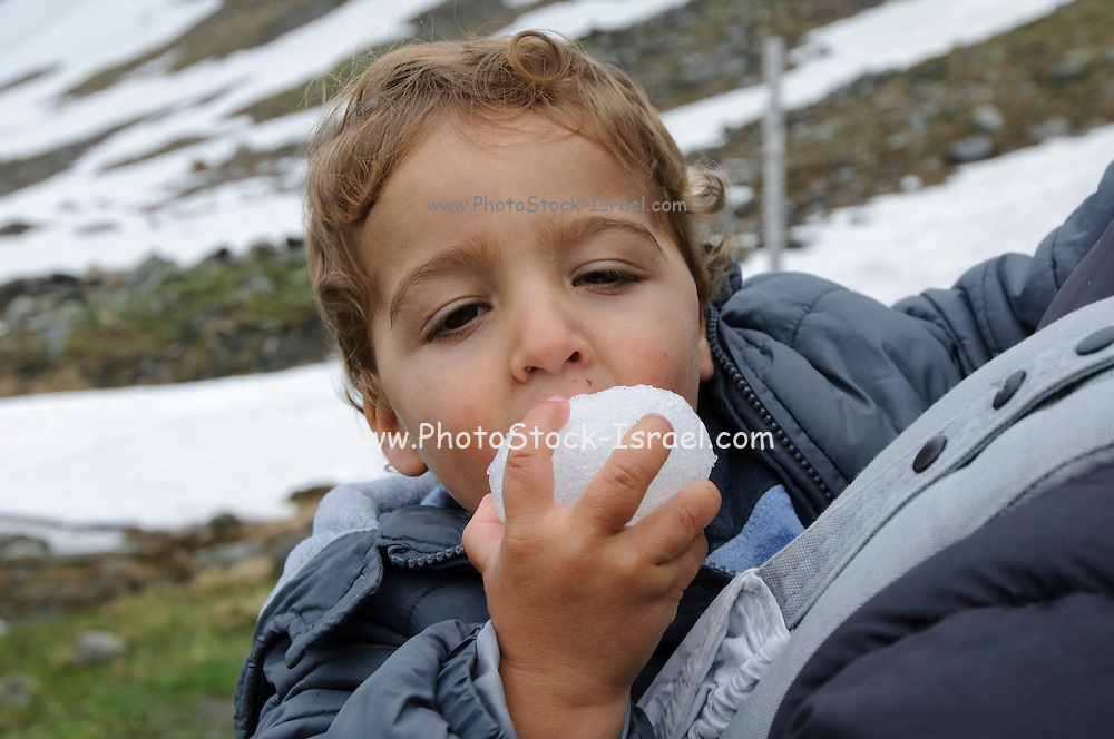 Boy of two eats a snowball Photogrpahed in the Austrian Alps