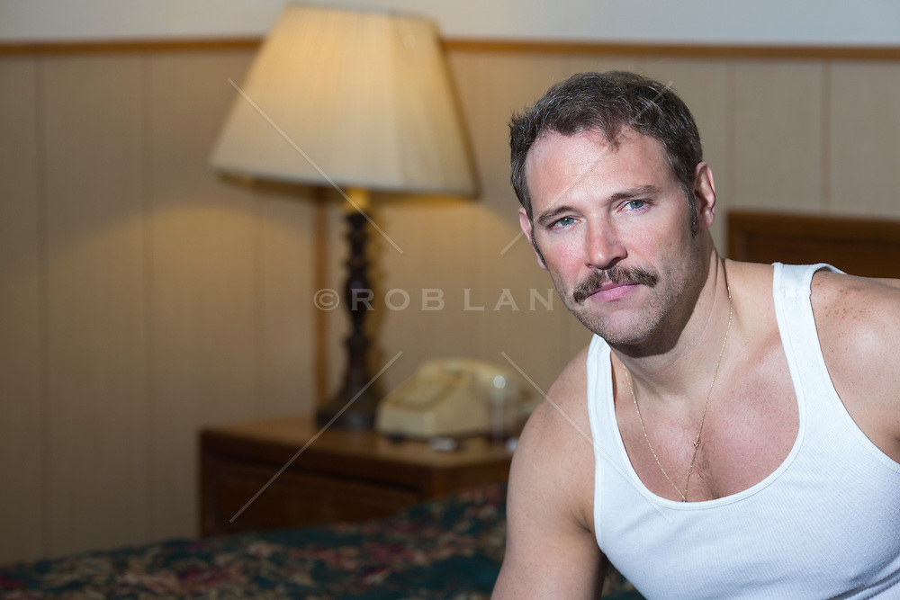 portrait of a man in a white sleeveless tee shirt in a cheap motel room