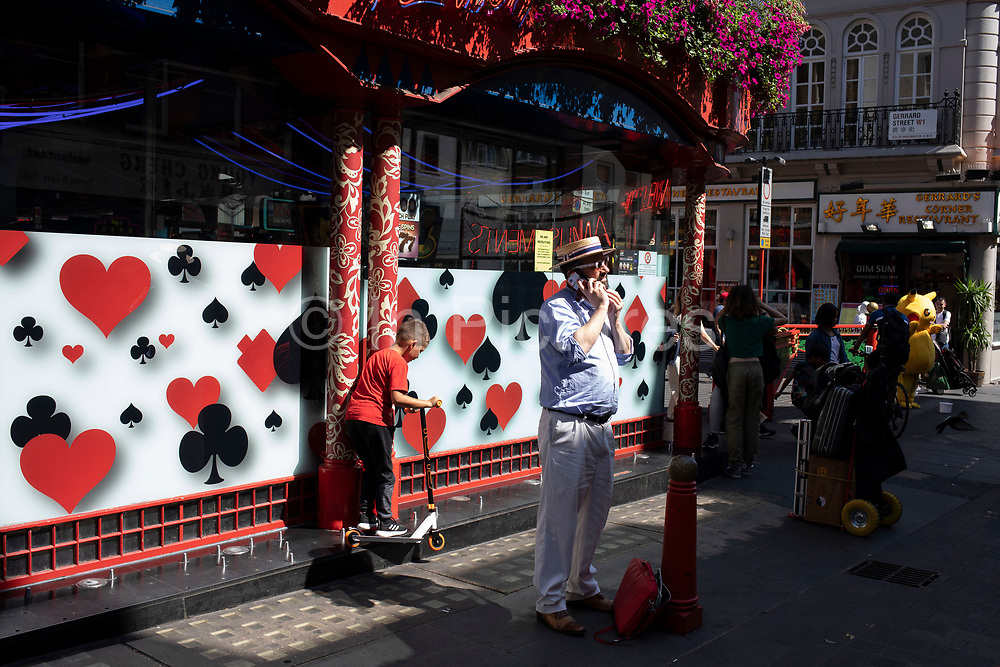 Street scene with a man wearing a straw boater hat as a young boy rides his scooter across a ledge outside a gaming shop in Chinatown in Soho, London, United Kingdom. The present Chinatown is in the Soho area occupying the area in and around Gerrard Street. It contains a number of Chinese restaurants, bakeries, supermarkets, souvenir shops, and other Chinese-run businesses and is in itself a major tourist destination.