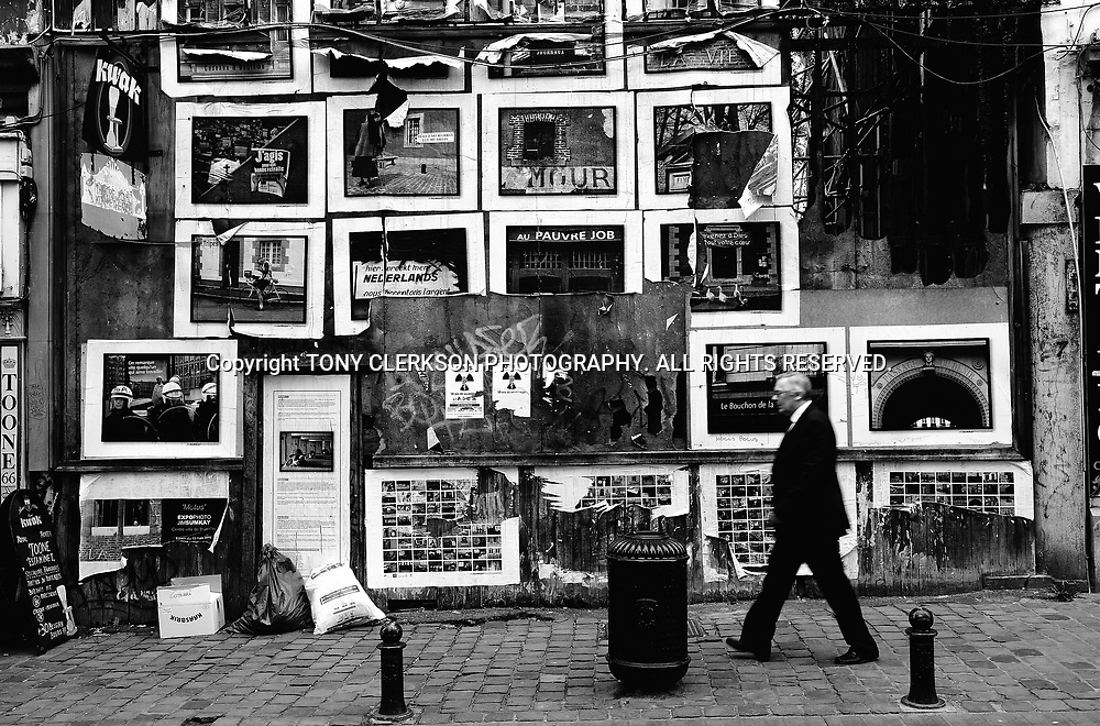 A businessman walks past posters on the wall of a fire-damaged building in Brussels town centre