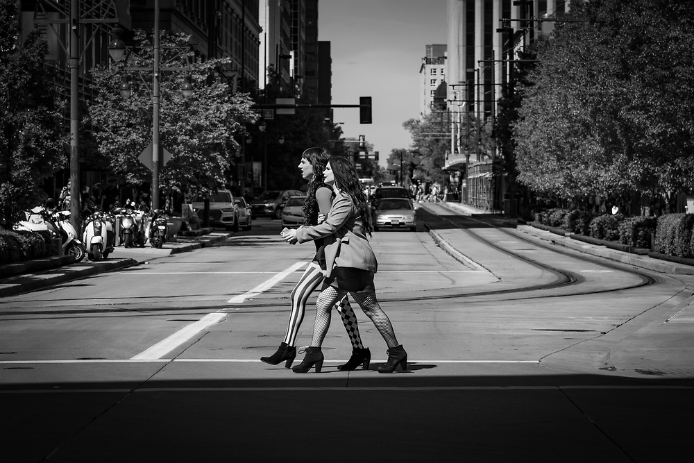 A couple walks hand in hand along 14th Street in downtown Denver.