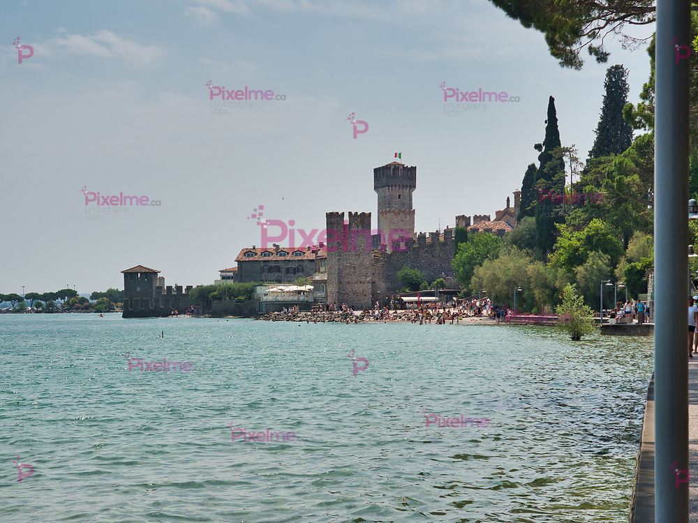View of the Scaligero Castle and its adjacent public beach from the panoramic promenade of Sirmione village on the shores of Lake Garda, Italy