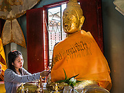 11 JULY 2014 - BANGKOK, THAILAND: A Thai woman makes merit by applying gold leaf to a statue of the Buddha in a chapel at Wat Mahabut for Asalha Puja Day. Asalha Puja is the day the Lord Buddha preached his first sermon to followers after attaining enlightenment. The day is usually celebrated by merit making and listening to a monks' sermons. It is also day before the start of the Rains Retreat, the three month period when monks stay in their temple for intense mediation and spiritual renewal.    PHOTO BY JACK KURTZ