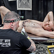 Jimmy Wong tattoo a client at The Great British Tattoo Show, London, UK