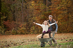 Father pushing happy daughter in wheelbarrow