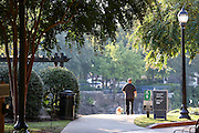 A man walks his dog along the Swamp Rabbit Trail and bike path in Falls Park on the Reedy River in downtown Greenville, South Carolina.